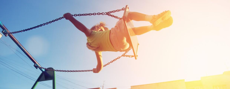 child swinging in the sun