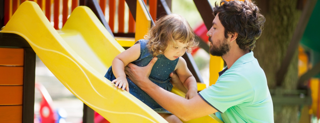 toddler on slide with parent